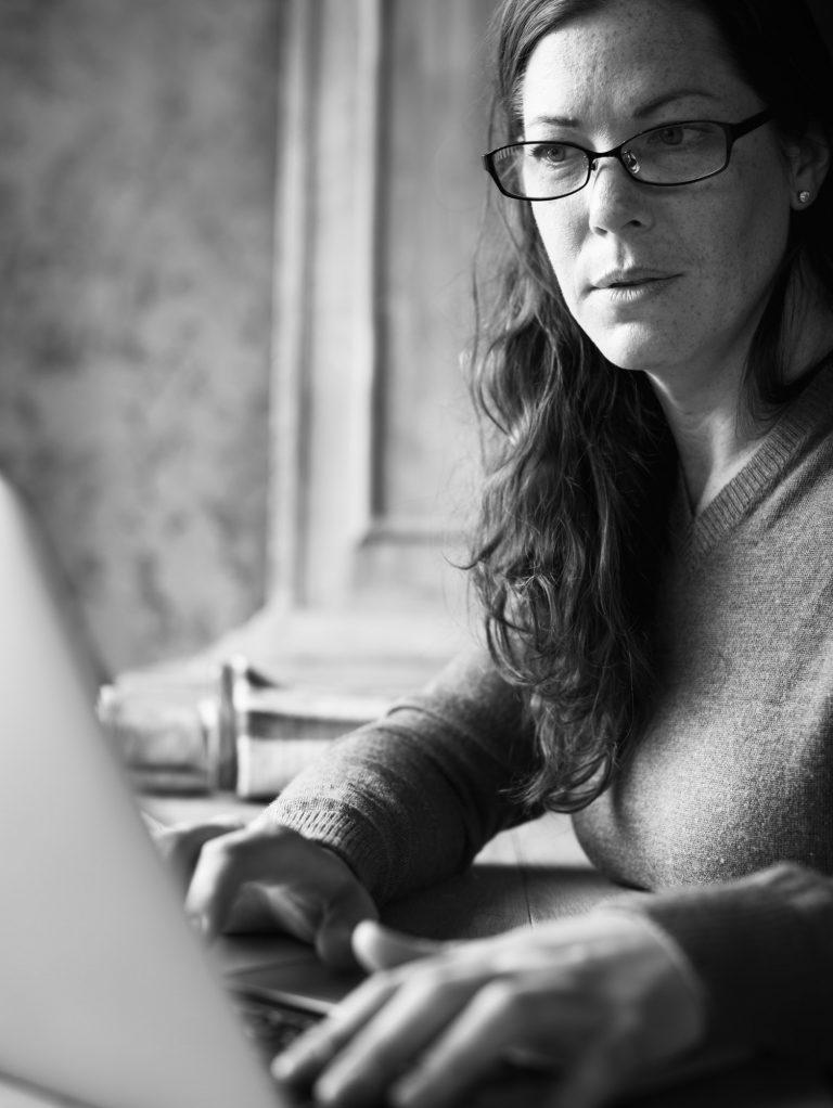 Caucasian woman using computer laptop grayscale